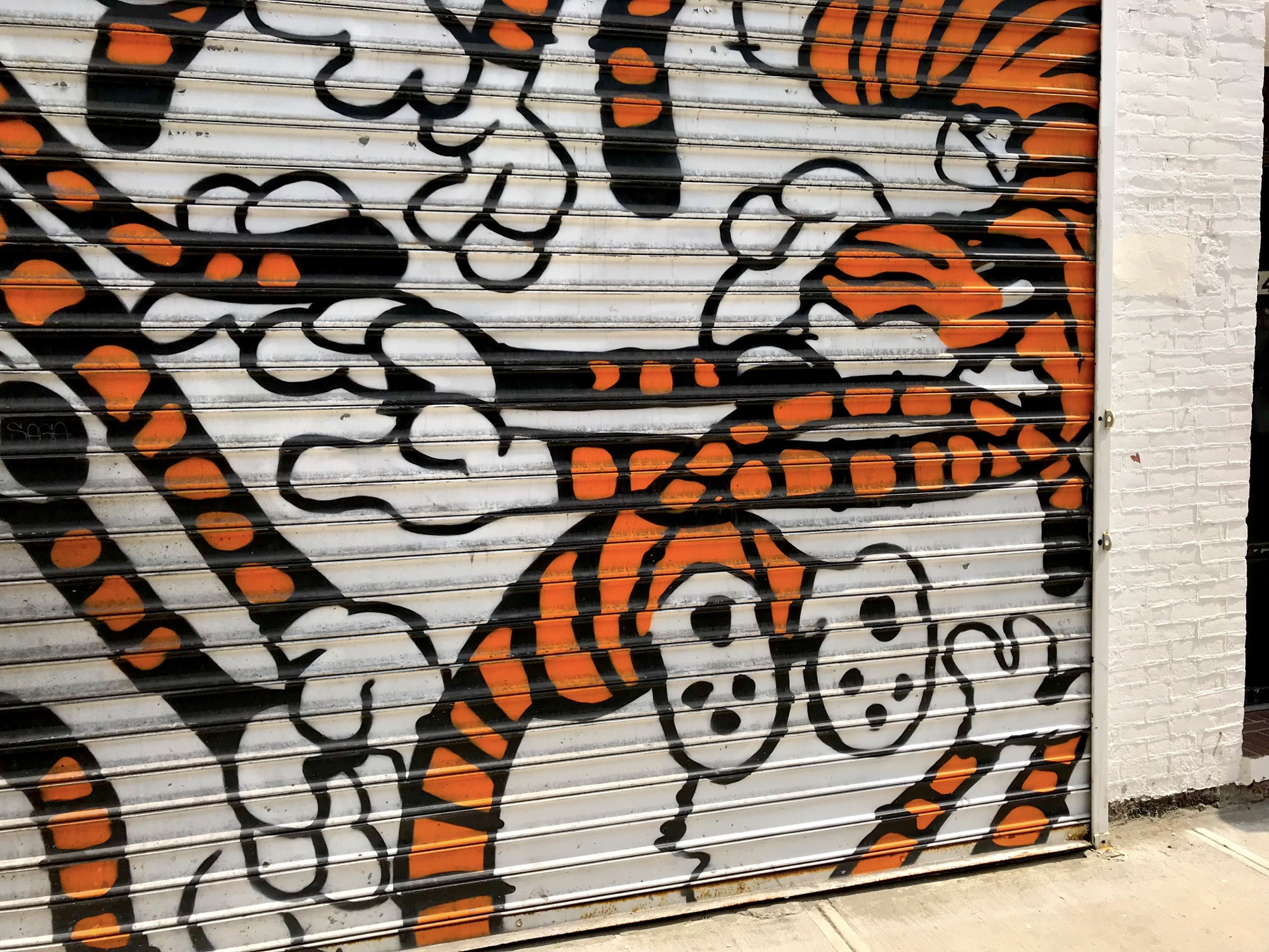 Photo of garage door with painting of Hobbes from Calvin and Hobbes.