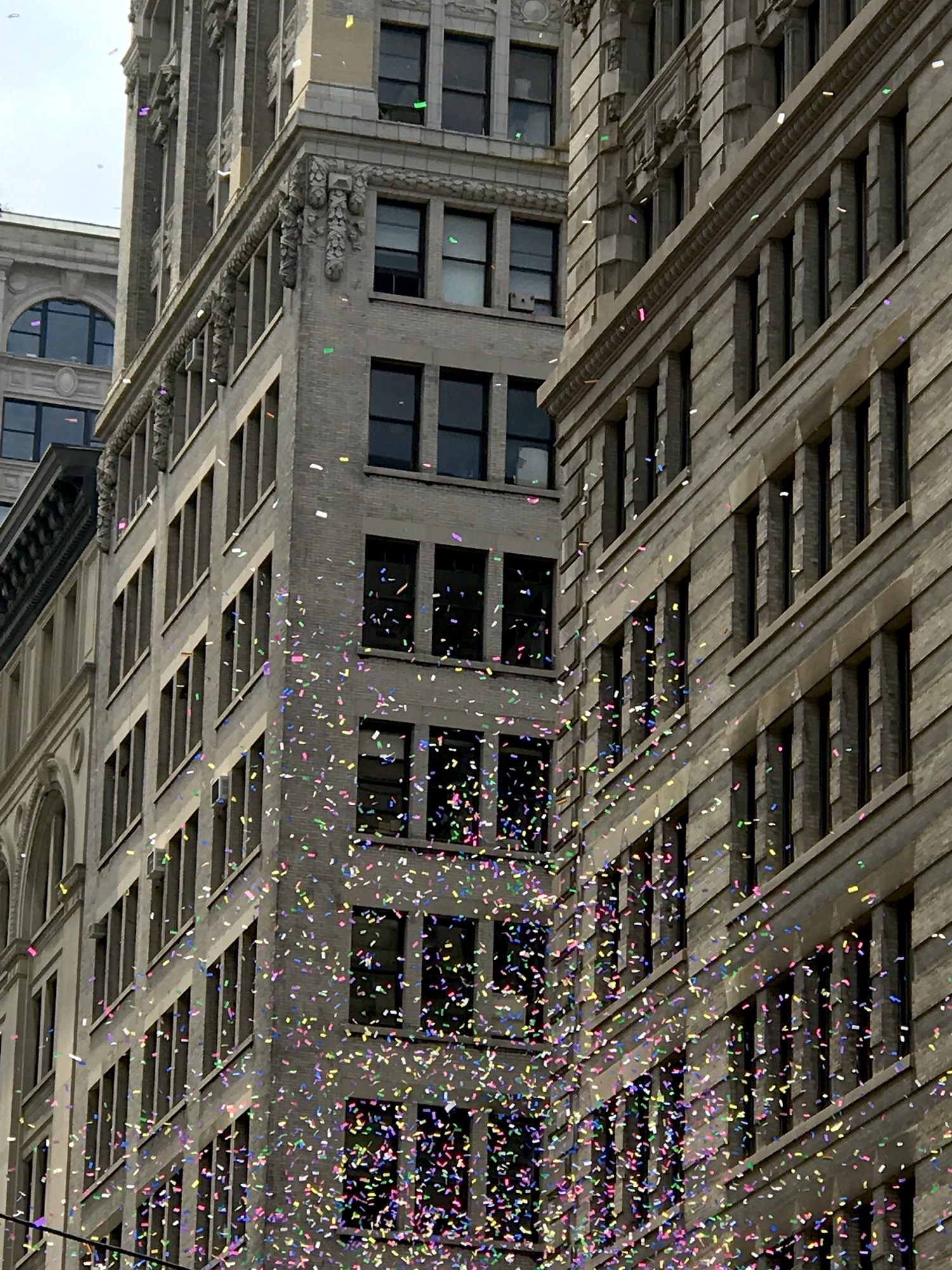 Photo of rainbow confetti against Fifth Avenue buildings.